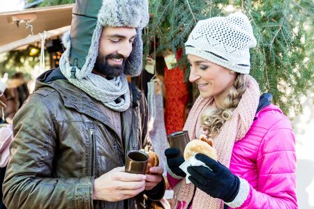 Woman and man eating and drinking on Christmas market, mulled wine and sausages Imagens