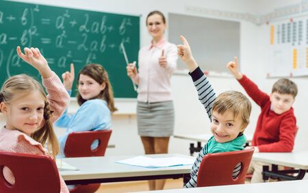 Students in class raising hands to answer a question they all know the answer of