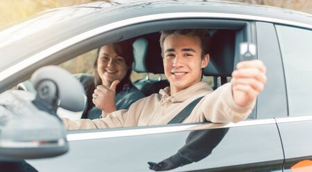 Happy student of driving school showing car keys after passing final test