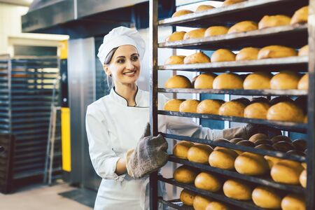 Baker woman rolling trays with fresh bread thru the bakery 스톡 콘텐츠