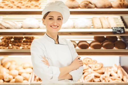 Sales woman in bakery shop standing in front of delicious bread in a shelf Imagens