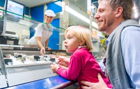 Family at the fish counter in a supermarket looking at what is on offer Reklamní fotografie