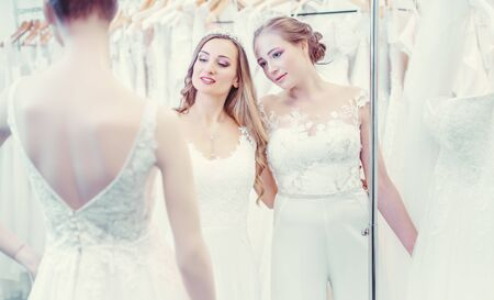 Two brides of same sex wedding couple looking at dress mannequin choosing what to wear