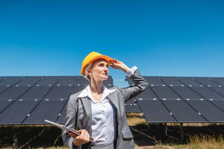 Businesswoman or investor inspecting her solar farm standing in front of photovoltaic panels