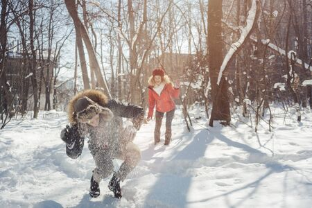Woman throwing snowball on her guy in winter in playful mood teasing him