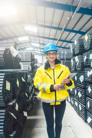 Woman working in logistics warehouse for building materials