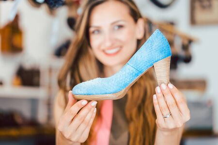 Happy woman shopping for shoes falls in love with blue high heels