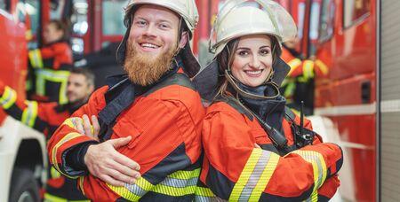Fire fighter man and woman standing together shoulder to shoulder