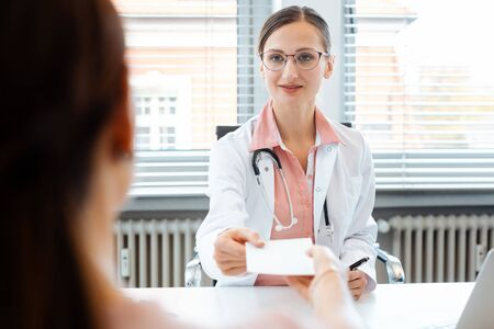 Doctor woman handing slip for prescription drug over to patient