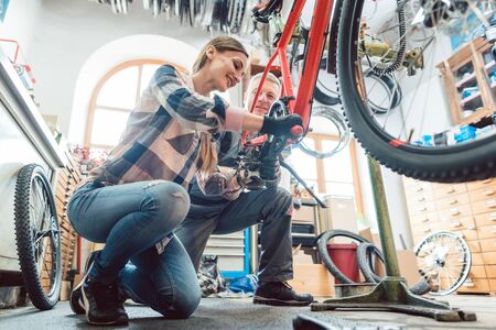 In a bike repair workshop with two bicycle mechanics, seen through tires of the machine