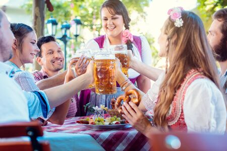 Cheerful group of friends toasting in Bavarian beer garden Banco de Imagens