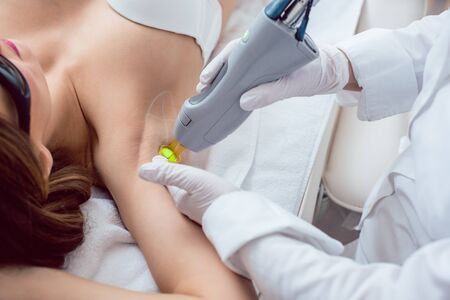 Woman during hair removal in the armpit region using modern laser technology