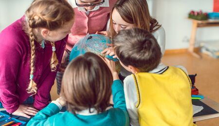 Pupils and teacher in geography class studying a globe together Banco de Imagens