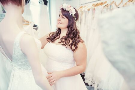 Woman as bride to be looking for bridal wear and dress in a wedding shop Banco de Imagens