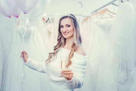 Bride to be in white with balloons in bridal wear shop toasting with glass of champagne