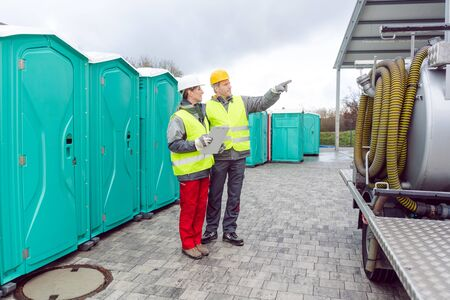 Workers inspecting mobile toilet before shipment to the customer