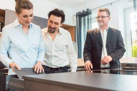 Salesman explaining details of new kitchen to couple of woman and man Stock Photo