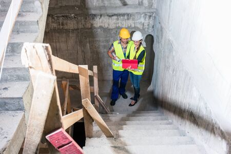 Construction worker and builder inspecting stairs in a building shell