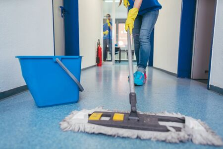 Close-up of cleaners moping the floor of a hall Zdjęcie Seryjne