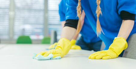 Close-up of cleaning team working in an office, banner cut