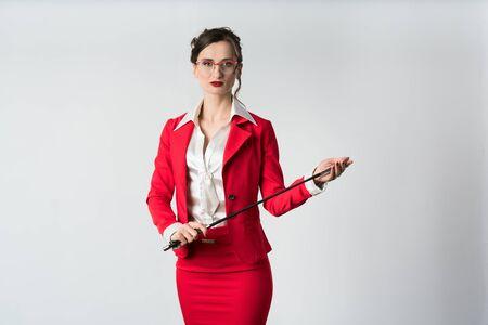 Femme d'affaires en costume rouge avec un fouet prêt à, eh bien, diriger Banque d'images