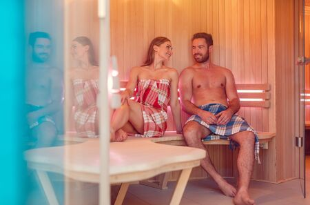 Woman and man sitting side by side in the heat of a spacious sauna
