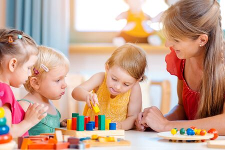 Group of children and teacher playing practical games in kindergarten Standard-Bild