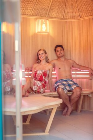 Couple of Caucasian woman and Asian man enjoying a very luxurious sauna