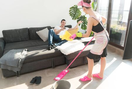 The wife must clean the house while her man is watching TV lounging on the couch