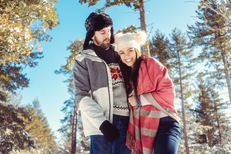 Winter couple in the forest enjoying the cold season