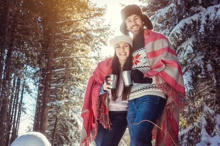 Woman and man on cold winter day warming up with hot tea amid snowy trees