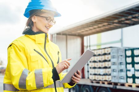 Supervisor checking contents of shipment to be sent by truck on her tablet computer