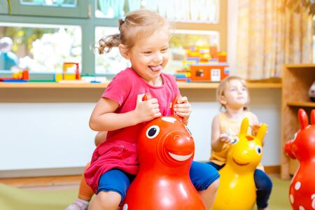 Little girls riding on red and yellow play horses in kindergarten
