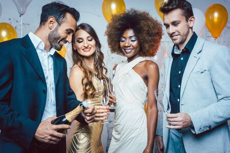 Man, on new year or birthday party opening bottle of champagne together with his friends