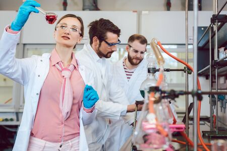 Three analytical chemists doing research in the lab, shot though the test tubes Stock fotó