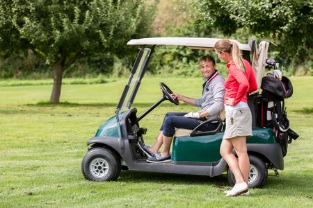 Fit young woman talking to male golfer sitting in the golf cart
