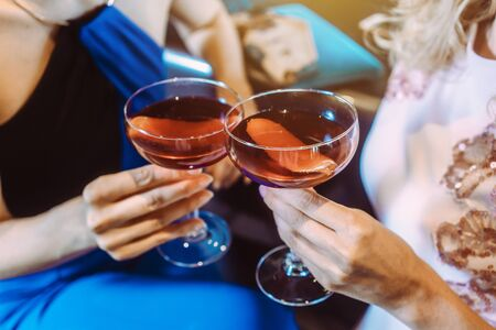 Close up on women holding cocktails in a bar toasting Standard-Bild