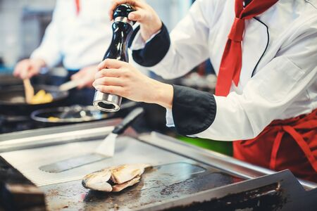 Crop of chef seasoning fish with pepper in the kitchen, another cook working in the background