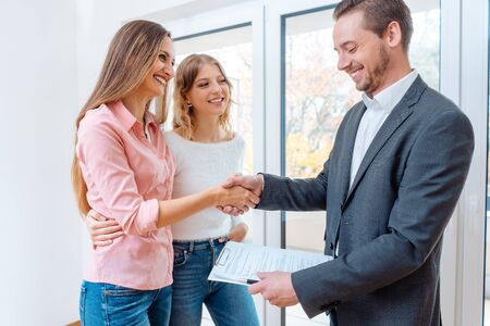Real estate broker shaking hands with two women tenants
