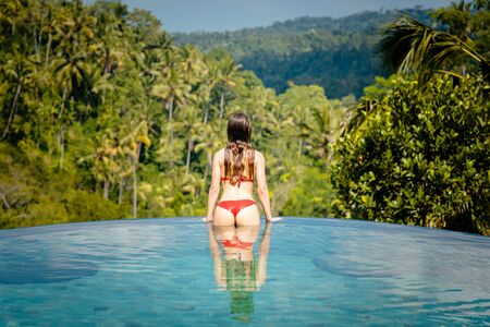 Woman in tropical swimming pool looking at the jungle from the water Stock fotó