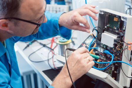 Electronics engineer man troubleshooting defects in a hardware product on his test bench 版權商用圖片
