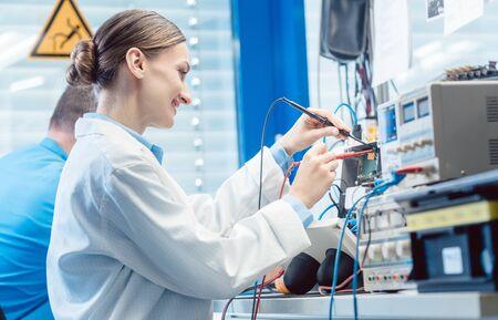Équipe d'ingénieurs, femme et homme, testant et mesurant ensemble un produit électronique en laboratoire