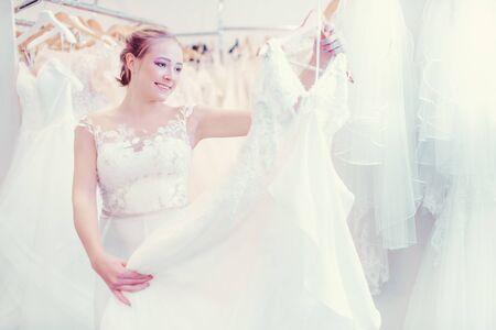 Jeune femme faisant du shopping dans une boutique de mariage pour une robe à porter en tant que mariée Banque d'images