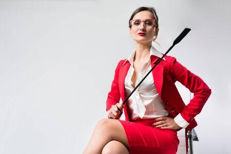 Arrogante Geschäftsfrau mit Peitsche in ihrem Stuhl im Büro Standard-Bild