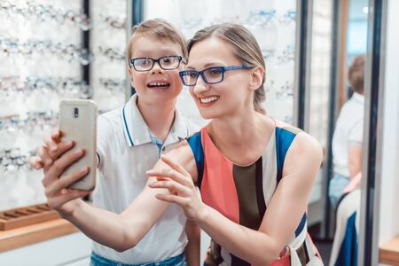 Mother and son taking selfie with new glasses at optometrist shop being happy