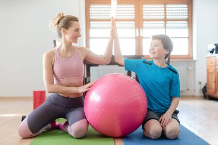 Mother and son giving each other a high-five after fitness exercise at home with pink ball