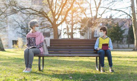 Großmutter und Enkel durch soziale Distanzierung auf der Parkbank getrennt