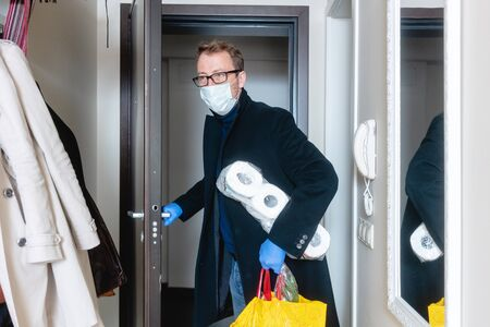 Man wearing medical mask coming home from shopping and hoarding with toilet paper Stock Photo