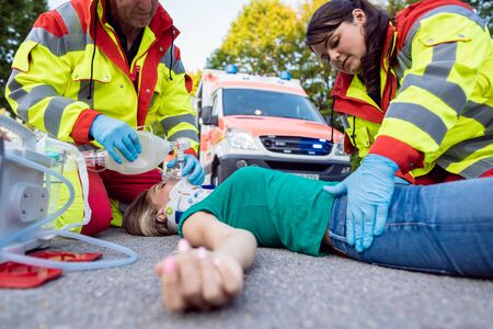 Emergency doctor ventilating injured woman after motorbike accident giving first aid Stock fotó