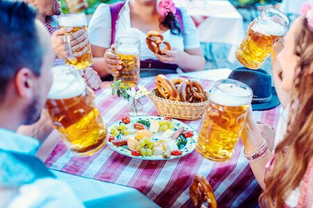 People enjoying food and drink in Bavarian beer garden on a sunny day